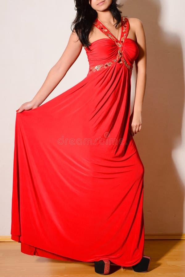 Schöner Brunette in einem roten Kleid mit Juwelen lizenzfreies stockfoto