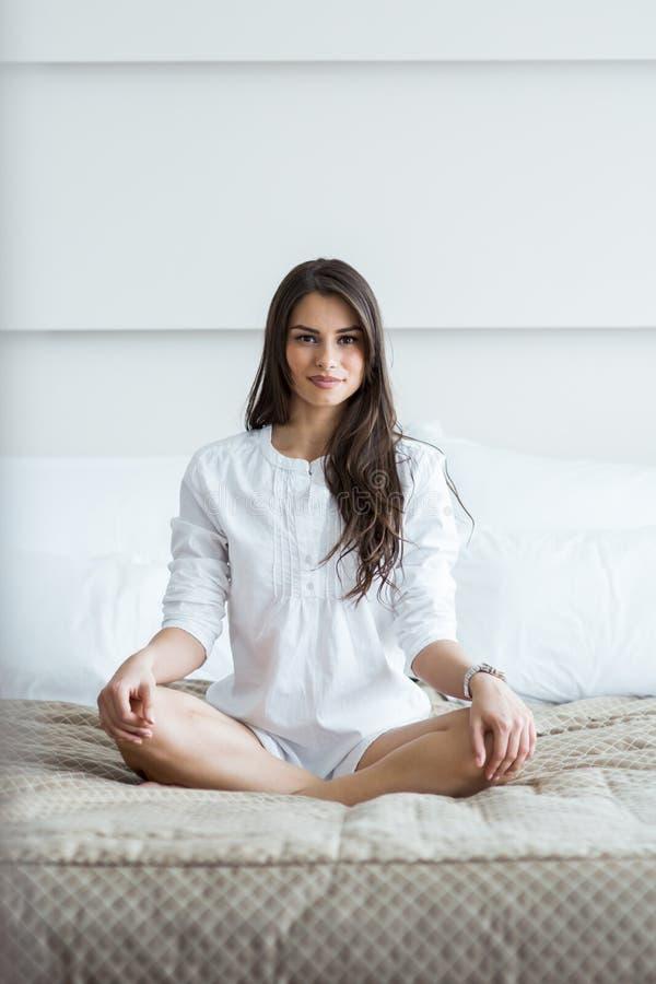 Schöner Brunette in einem weißen Hemdschneidersitz, der auf einem Bett aufwirft lizenzfreie stockfotos