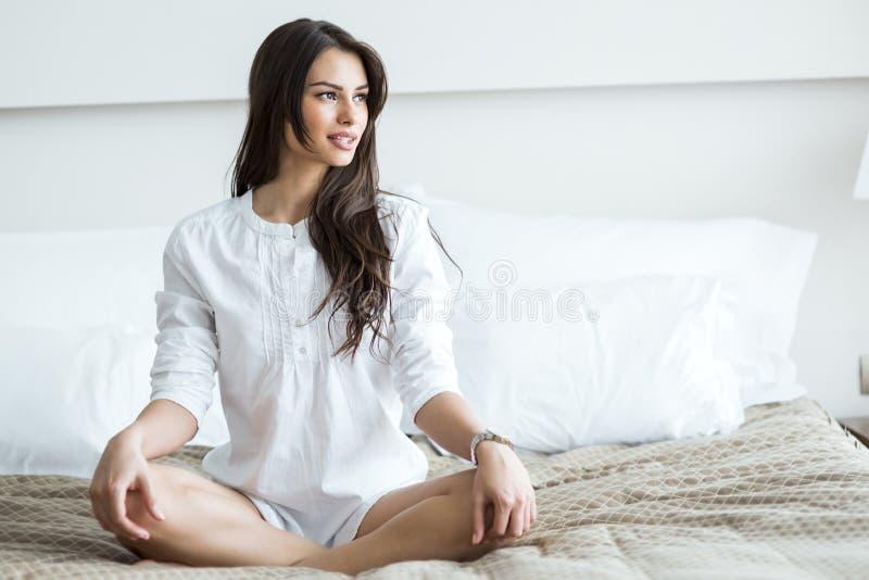 Schöner Brunette in einem weißen Hemdschneidersitz, der auf einem Bett aufwirft stockfotografie