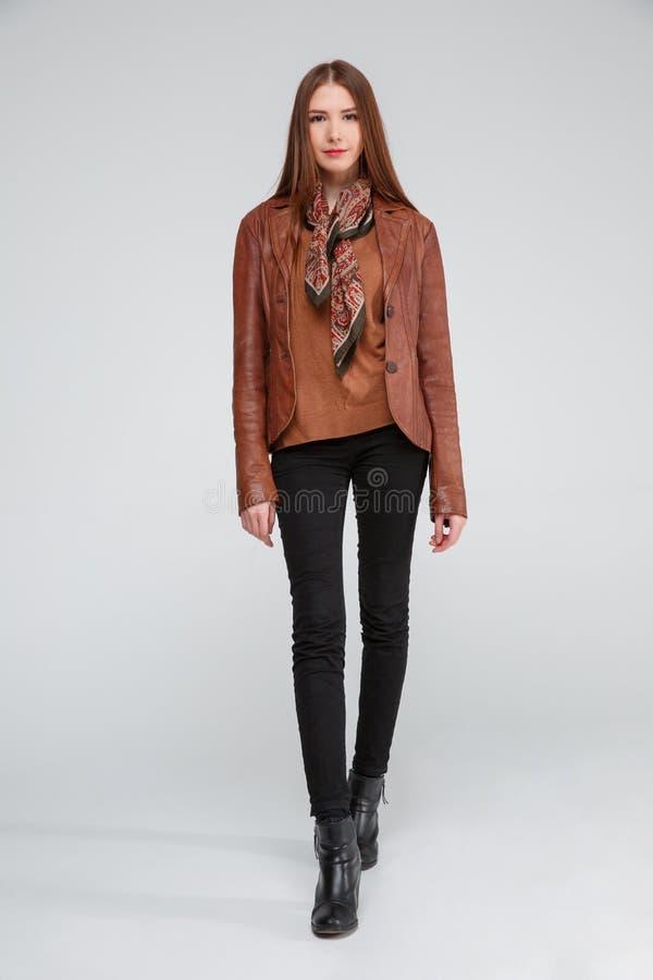 Schöner Brunette in einer braunen Lederjacke, die mit ihren Händen unten auf einem grauen Hintergrund aufwirft lizenzfreie stockfotografie