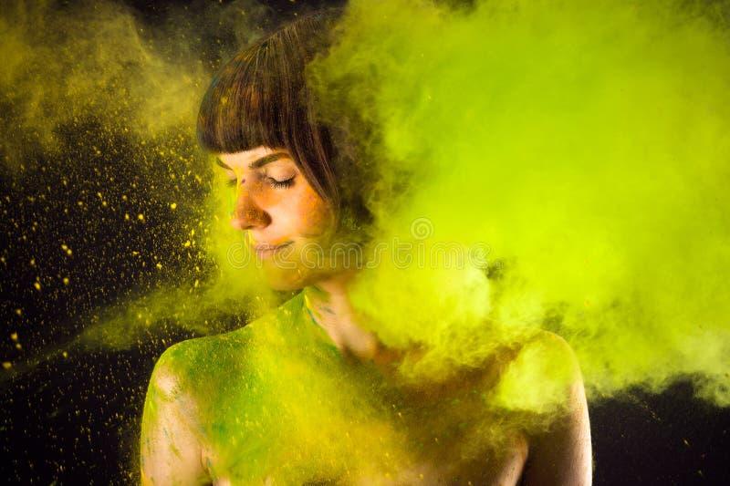 Schöner Brunette in einer grünen Farbe Holi stockbilder