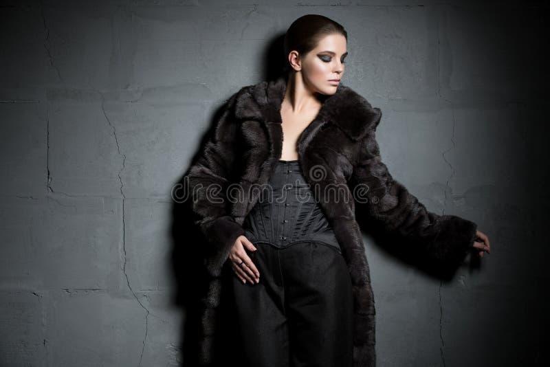 Schöner Brunette im Pelzmantel in der Dunkelheit lizenzfreie stockbilder