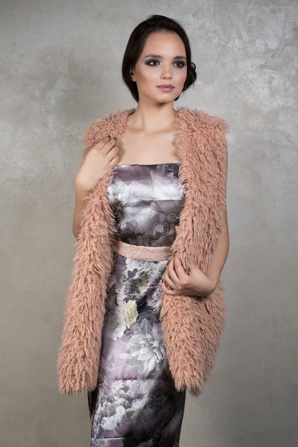 Schöner Brunette mit Abendmake-up in einem silbernen Kleid mit floristical Druck und beige Mantel steht auf einem grauen Hintergr stockfotos