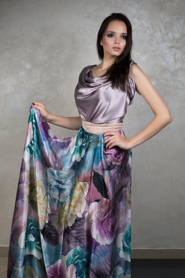 Schöner Brunette mit Abendmake-up im purpurroten Seidenkleid, das auf dem grauen Hintergrund anhebt Handrand steht lizenzfreies stockbild