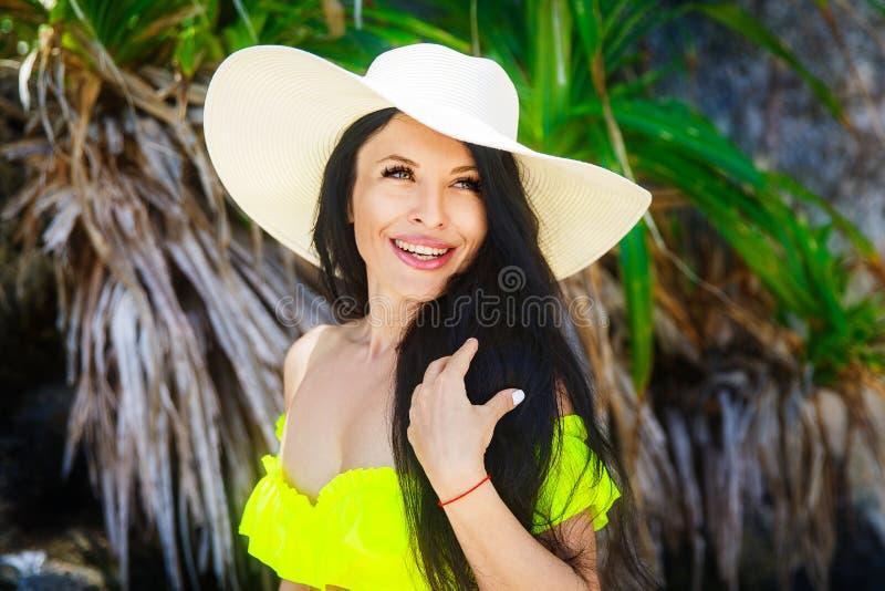 Schöner Brunette mit dem langen Haar im Bikini und im Strohhut auf stockfotografie