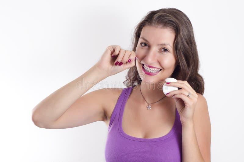 Schöner Brunette mit den Klammern, die Zähne flossing sind stockfoto