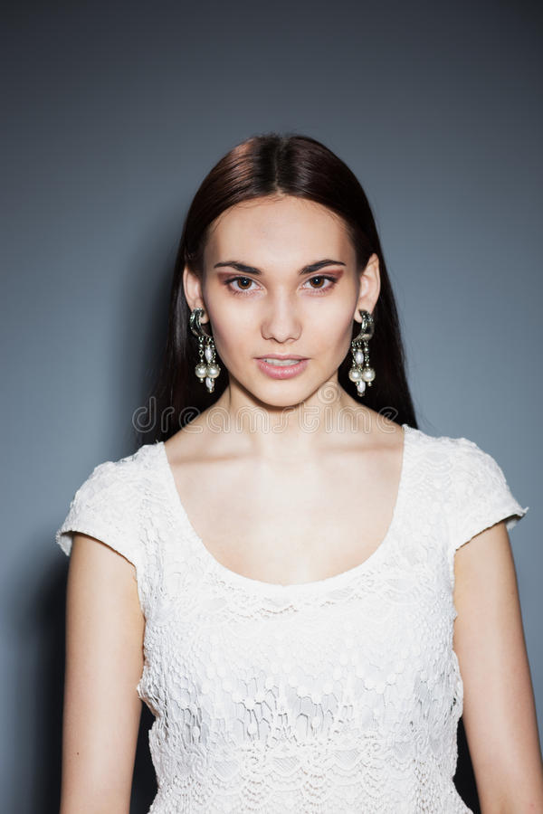 Schöner Brunette mit großen Ohrringen lizenzfreies stockbild