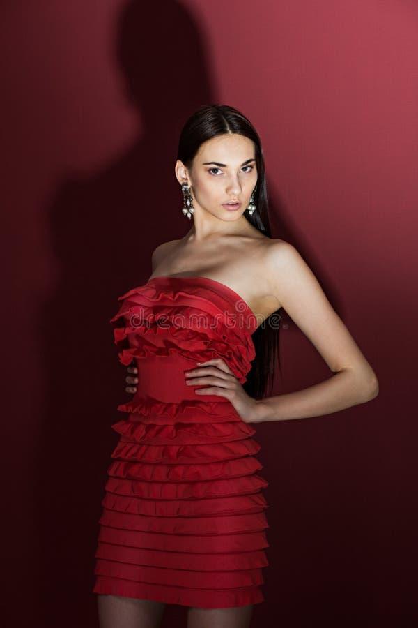 Schöner Brunette mit herein einem roten Kleid stockfotos