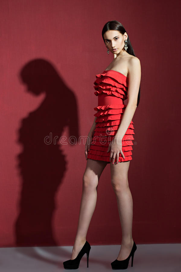 Schöner Brunette mit herein einem roten Kleid lizenzfreies stockfoto