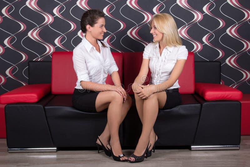 Schöner Brunette und blonde Unterhaltung auf dem Sofa stockfotos