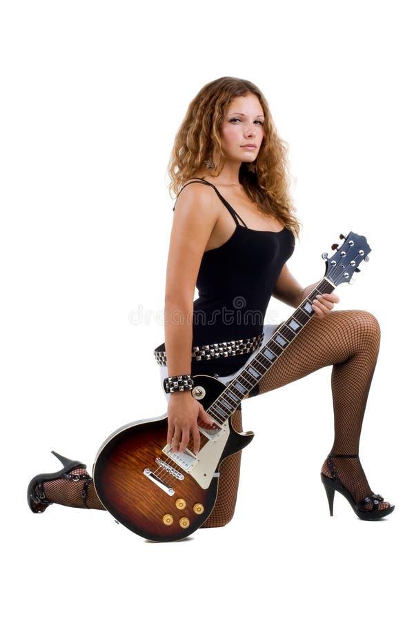 Schöner Brunette wirft im Studio mit einer Gitarre auf lizenzfreies stockbild