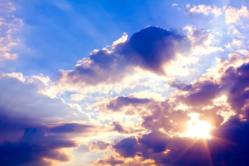 Schöner bunter Sonnenuntergang mit Sonnenstrahlen und blauem Himmel mit Wolken lizenzfreie stockfotografie