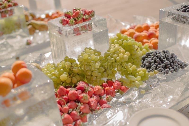 Schöner Catering von organischen natürlichen frischen Früchten ausgebreitet auf dem Eis für die Feier des Ereignisses, Hochzeit stockfotografie