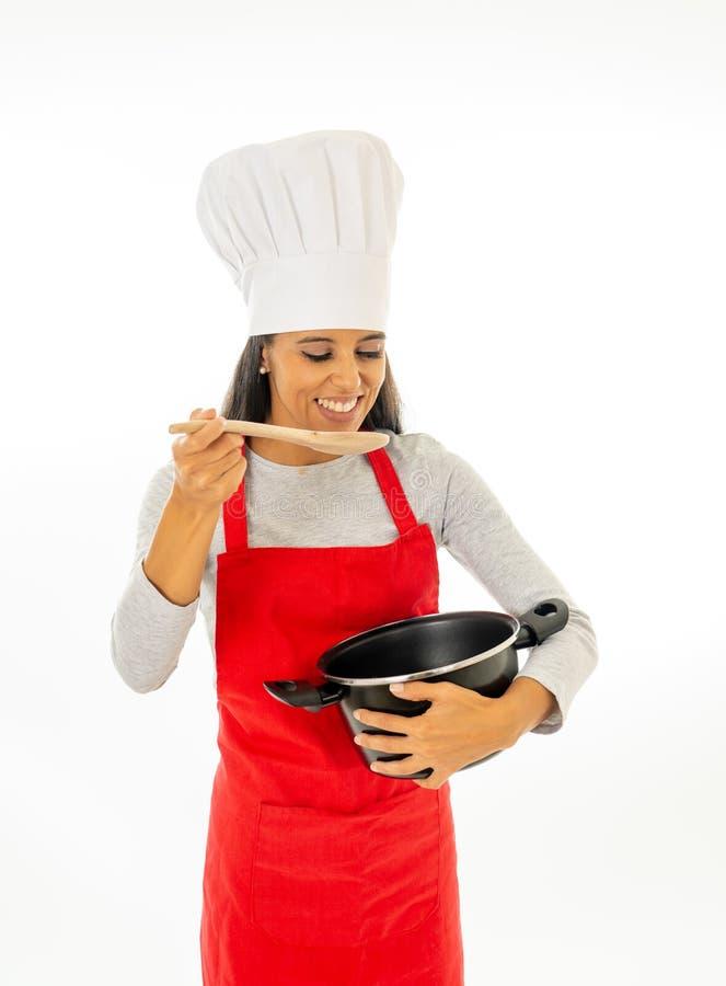 Schöner Chef der jungen Frau, der einen Topf versucht ihr köstliches Lebensmittel mit hölzernem Löffel hält stockbilder