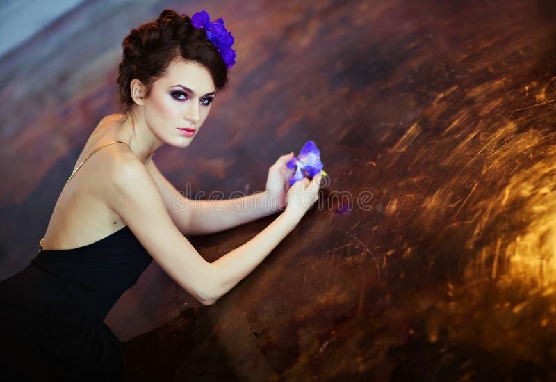 Schöner dünner Brunette mit Blumen in ihrem Haar, das auf dem Florida liegt lizenzfreie stockfotografie