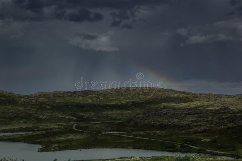 Schöner düsterer dunkler stürmischer Himmel und Regenbogen über einem grünen Tal stockfotos