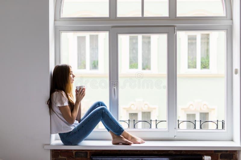 Schöner Daydreamer Schöne junge Frau, die Kaffeetasse mit Lächeln beim am Fensterbrett zu Hause sitzen hält lizenzfreies stockbild