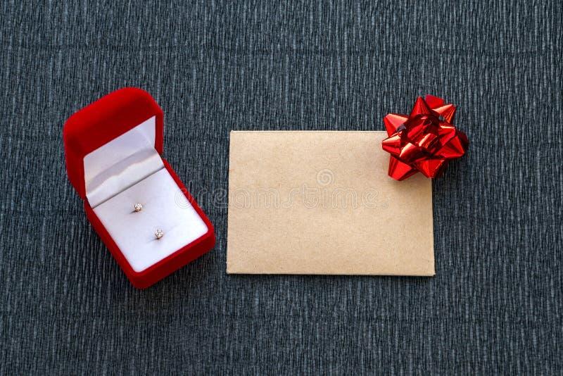 Schöner des Rotes Kasten jewely mit Ohrringen und Umschlag mit Bogen stockfotos