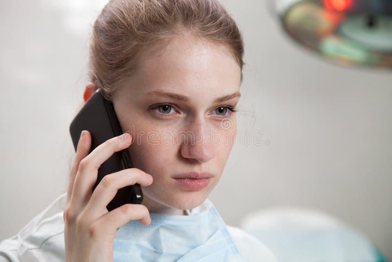 Schöner Doktor, der ein intelligentes Telefon verwendet stockfotografie