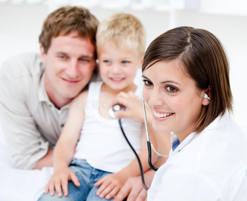 Schöner Doktor, der einen Jungen mit seinem Vater überprüft stockfotos