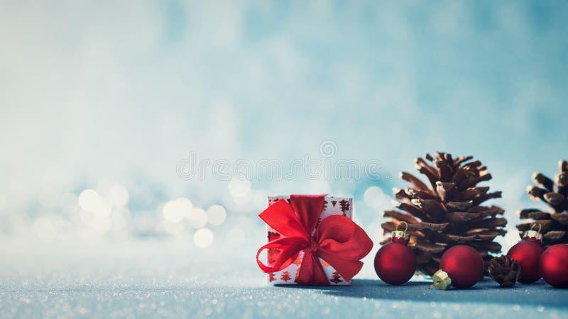 Schöner einfacher Weihnachtshintergrund mit Kopienraum Nettes Weihnachtsgeschenk, rote Verzierungen und Kiefernkegel auf blauem H lizenzfreie stockbilder