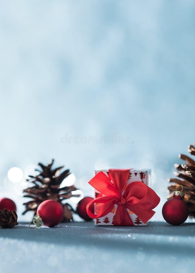 Schöner einfacher Weihnachtshintergrund mit Kopienraum Nettes Weihnachtsgeschenk, rote Verzierungen und Kiefernkegel auf blauem H lizenzfreie stockfotos