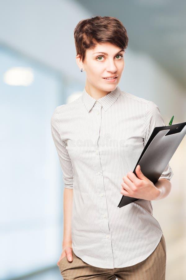 Schöner erfolgreicher FrauenBüroangestellter mit einem Ordner lizenzfreie stockbilder