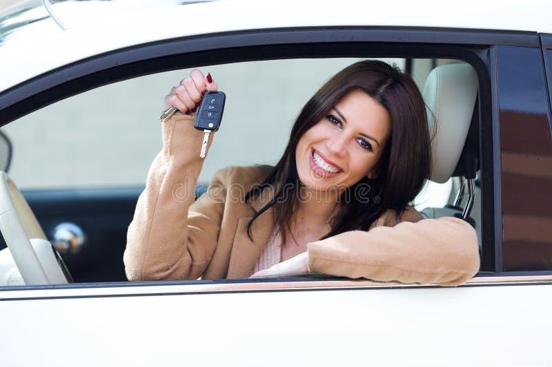 Schöner Fahrer der jungen Frau, der Selbstschlüssel in ihrem Neuwagen hält stockfotografie
