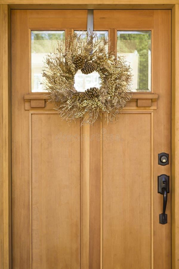 Schöner, fantastischer, eleganter Goldweihnachtskranz, der an der hölzernen Haustür hängt Ferienhausdekorationen stockbild