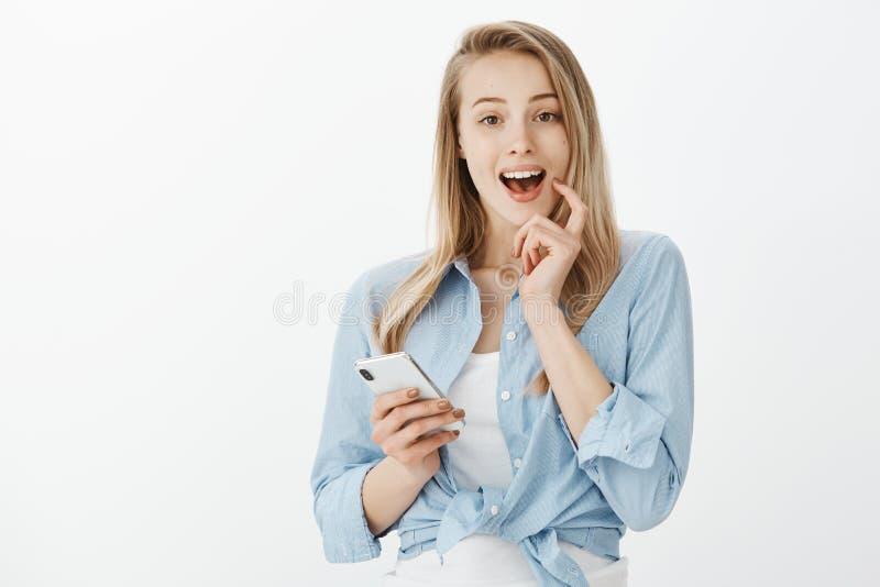 Schöner faszinierter blonder weiblicher Mitarbeiter in der stilvollen Ausstattung, die Finger auf Lippe beim breit lächeln hält stockfoto