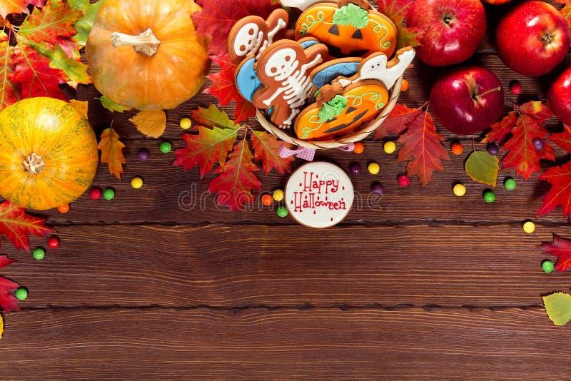 Schöner festlicher Hintergrund für Halloween mit Korblebkuchen, -Herbstlaub, -beeren und -süßigkeit auf einem Holztisch stockbild