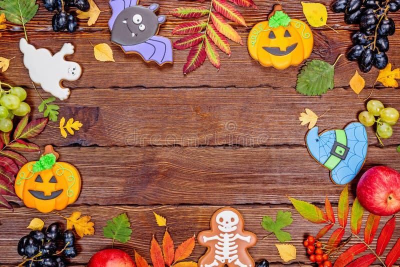 Schöner festlicher Hintergrund für Halloween mit Lebkuchen, Herbstlaub, Beeren und Süßigkeit auf einem Holztisch Freier Raum stockfotos