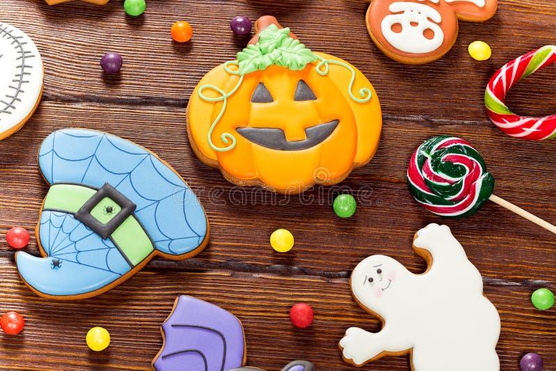 Schöner festlicher Hintergrund für Halloween mit Lebkuchen, Süßigkeit, Herbstlaub und Beeren auf einem Holztisch stockbilder