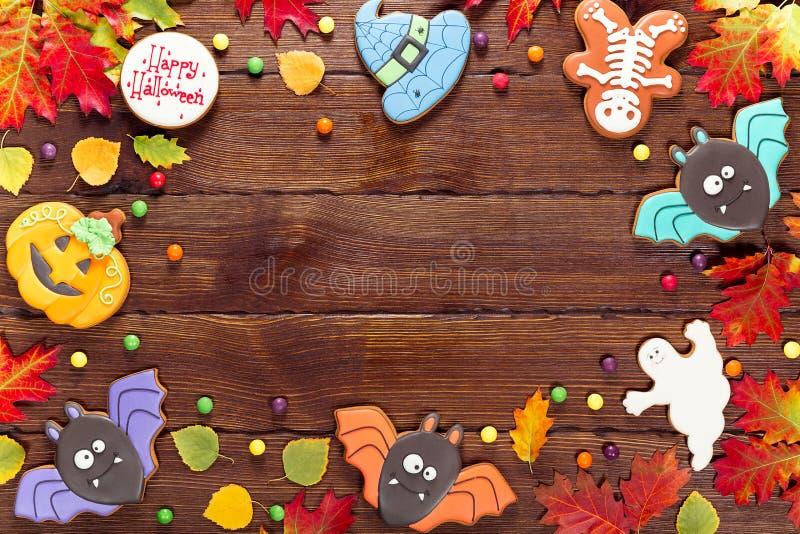 Schöner festlicher Hintergrund für Halloween mit Lebkuchen, Süßigkeit, Herbstlaub und Beeren auf einem Holztisch lizenzfreies stockbild