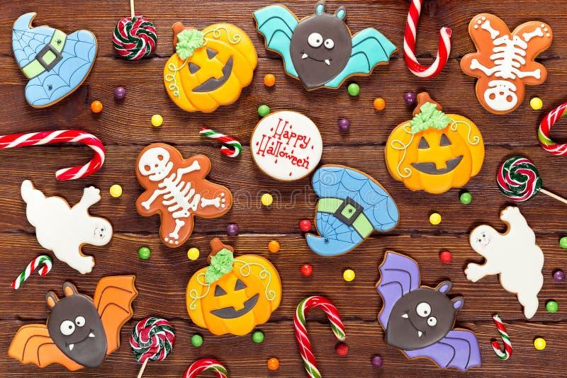 Schöner festlicher Hintergrund für Halloween mit Lebkuchen, Süßigkeit, Herbstlaub und Beeren auf einem Holztisch stockfotos