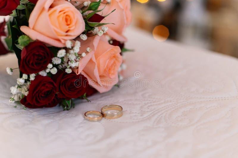 Schöner frischer Heiratsblumenstrauß mit Ringen auf einem weißen Bett lizenzfreie stockfotografie