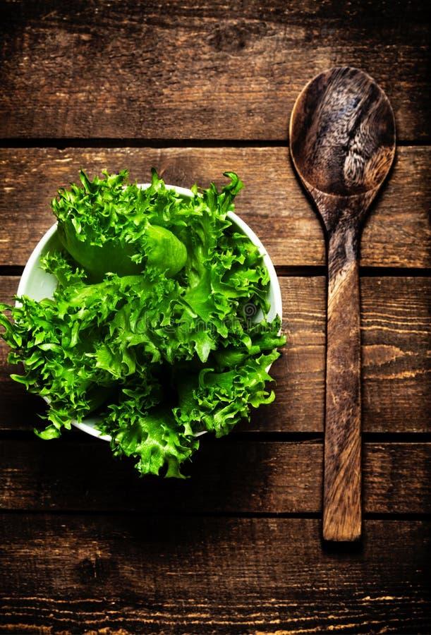 Schöner frischer Salat in einem Teller mit hölzernem Löffel über Weinlese flehen an stockfotografie