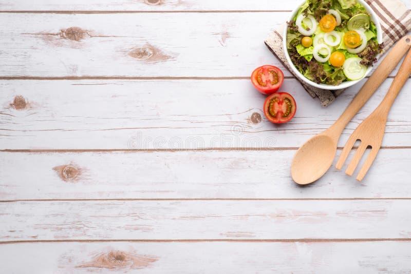 Schöner frischer Salat in einem Teller mit hölzernem Löffel über Weinlese flehen an lizenzfreies stockfoto