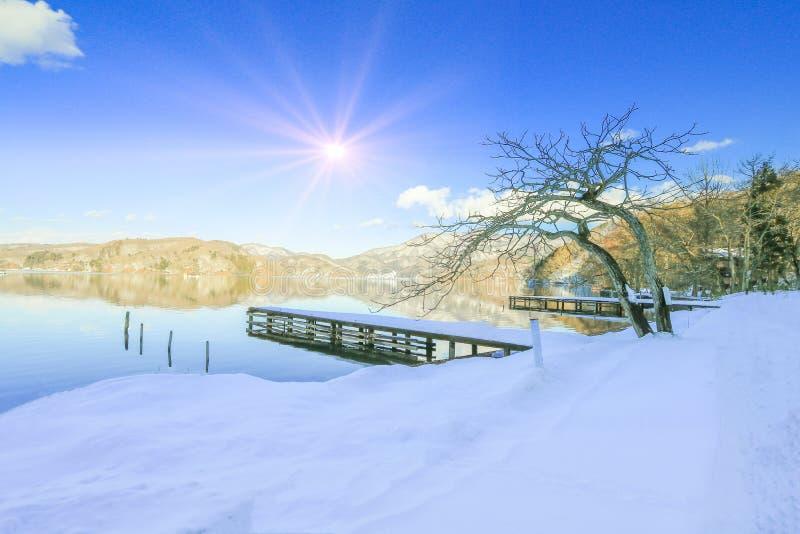 Schöner frischer Schnee im Winter um den Bergsee und Baum mit Hintergrund des Sonnenaufgangs und des blauen Himmels, Präfektur Na stockfotografie