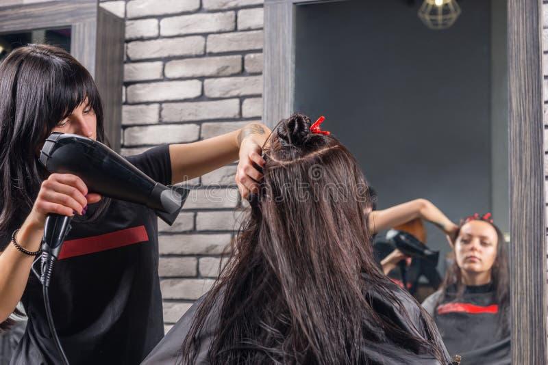 Schöner Friseur mit den tätowierten Händen unter Verwendung eines Haartrockners an lizenzfreie stockbilder