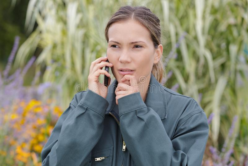 Schöner Gärtner der jungen Frau am Telefon lizenzfreie stockbilder