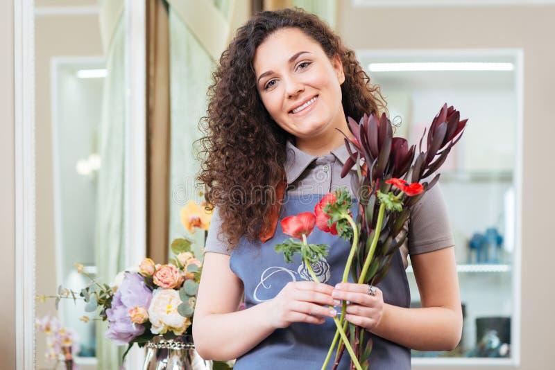 Schöner gelockter Frauenflorist, der im Blumenladen steht lizenzfreies stockfoto