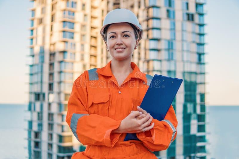 Schöner Geschäftsfrauingenieur, der orange Overall trägt stockfotos