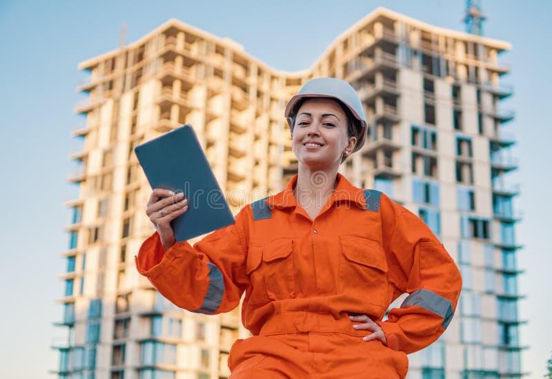 Schöner Geschäftsfrauingenieur, der orange Overall trägt lizenzfreie stockfotografie
