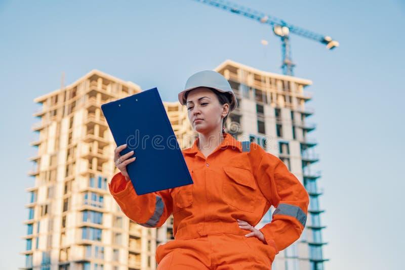 Schöner Geschäftsfrauingenieur, der orange Overall trägt lizenzfreies stockbild