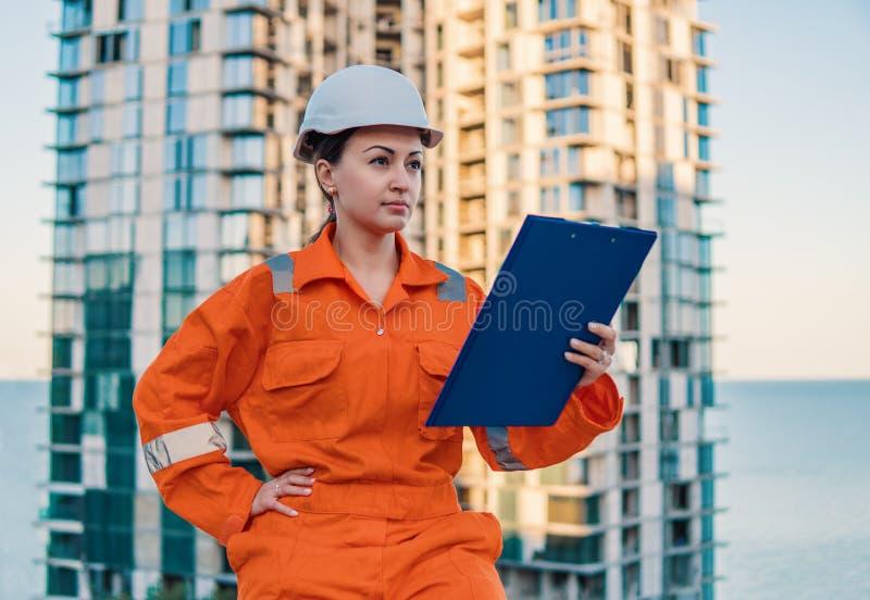 Schöner Geschäftsfrauingenieur, der orange Overall trägt lizenzfreies stockfoto