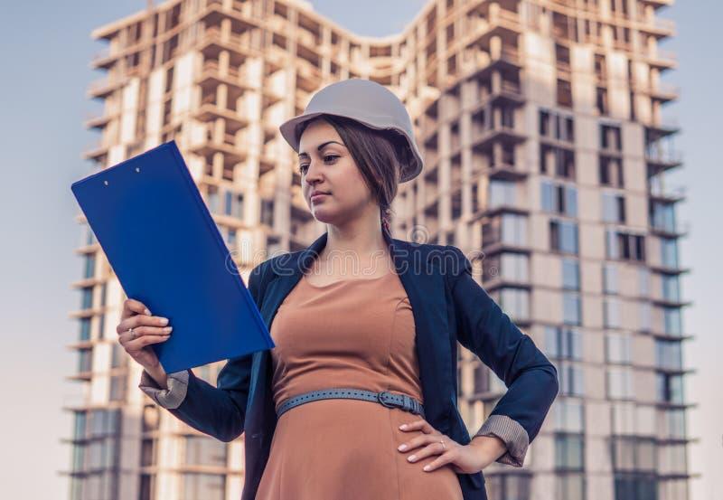 Schöner Geschäftsfrauingenieur steht mit Planpapieren stockbild