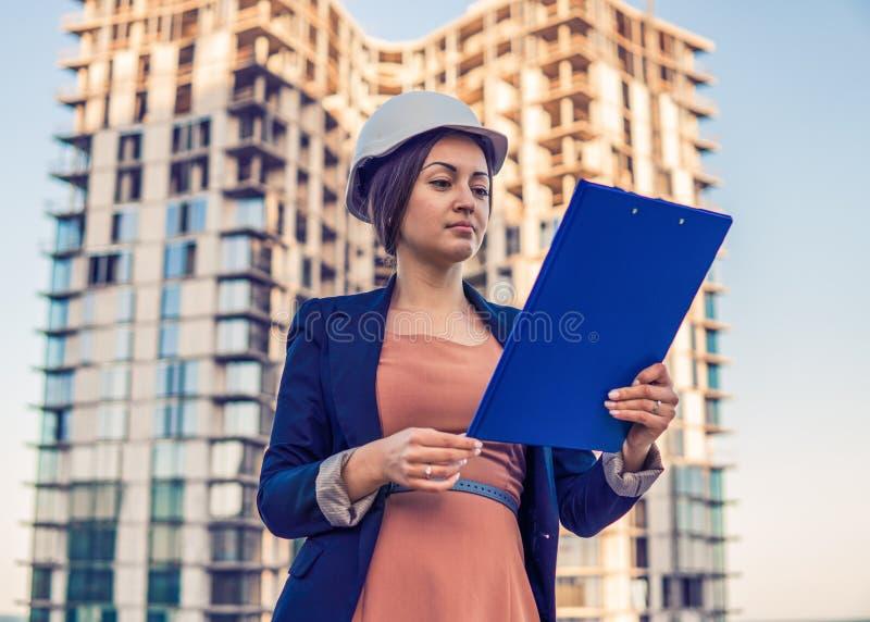 Schöner Geschäftsfrauingenieur steht mit Planpapieren stockfotografie