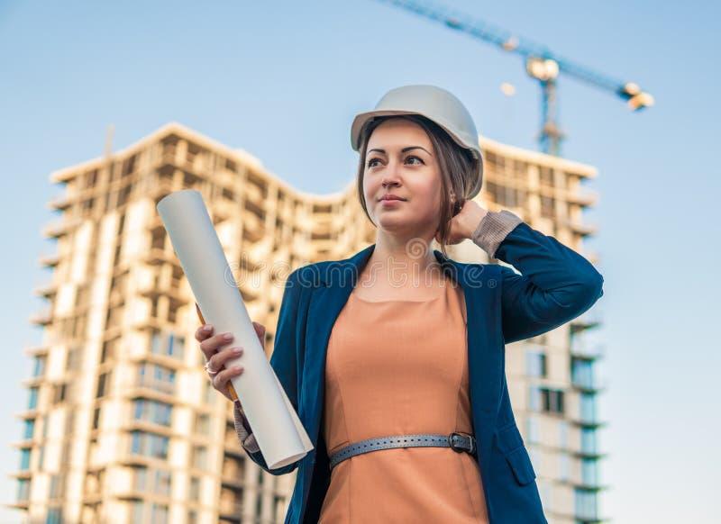 Schöner Geschäftsfrauingenieur steht mit Planpapieren lizenzfreies stockfoto