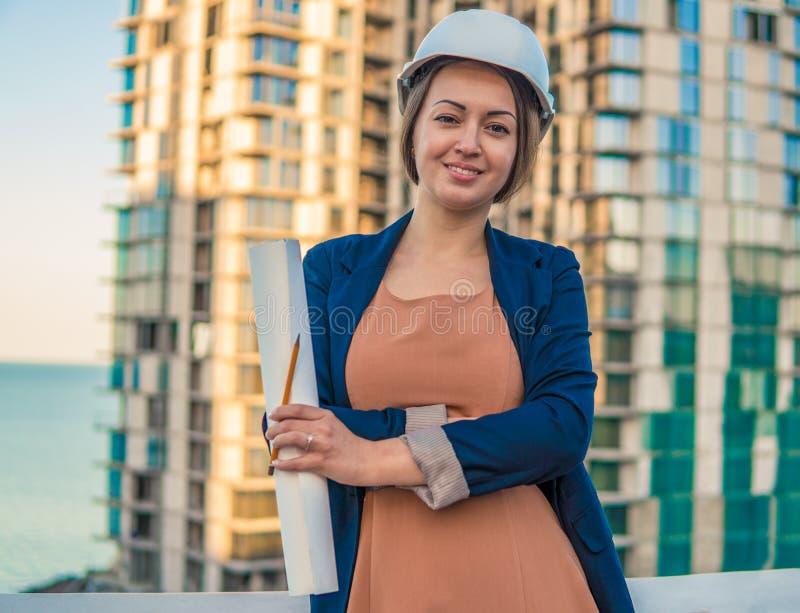Schöner Geschäftsfrauingenieur steht mit Planpapieren lizenzfreie stockbilder